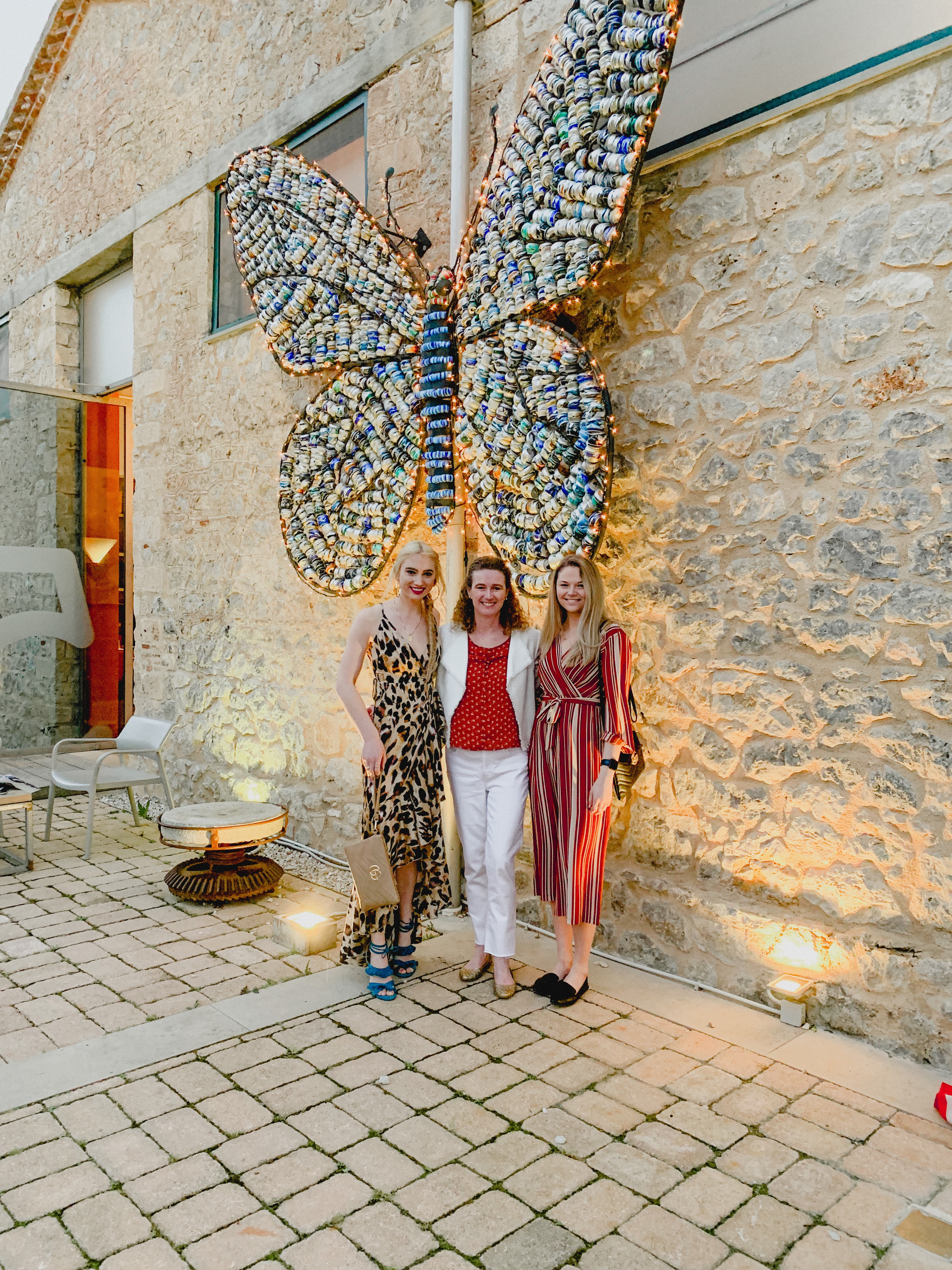 3 People standing in front of a butterfly statue at Fougaro Cultural Center